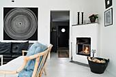 Kamin in weißem Wohnzimmer mit schwarzer Ledercouc und Rattansofa