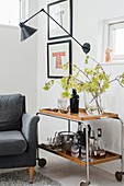 Armchair and drinks trolley in corner of room with white walls