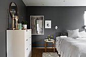 Double bed and white chest of drawers in bedroom with dark grey walls