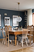 Wooden tables and chairs with fur blankets in dining room with blue walls
