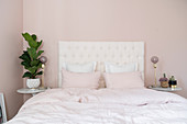 Double bed with white headboard in pale pink bedroom