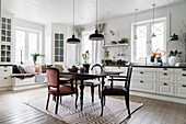 Antique dining table and chairs with window seat in background in white kitchen-dining room