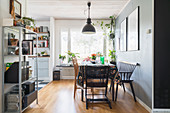 Dining area with grey wall and parquet floor in open-plan kitchen with metal shelves in foreground