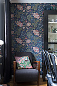 Cushion on armchair against floral wallpaper in dining area