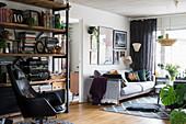 Schwarzer Ledersessel vor offenem Regal im Wohnzimmer, im Hintergrund helles Polstersofa