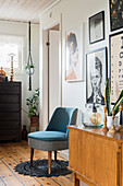 Retro sideboard and easy chair below collection of pictures