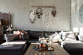 Coffee table, sofa, dreamcatchers on wall, armchair and screen in living room with pale grey walls