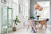 Tisch mit Schalenstühlen und Vitrinenschrank in hellem Esszimmer