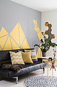 Black leather couch and side tables in living room with grey-and-yellow wall
