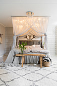 Double bed below canopy with lights and wooden bench in pale bedroom