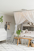 Double bed below canopy with fairy lights, wooden bench and bureau in pale bedroom