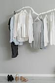 Kleidungsstücke hängen an DIY-Kleiderstange aus weiß gestrichenem Ast