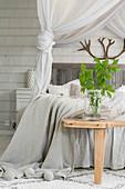 Glasgefäß mit Blätterzweig auf Holzbank am Doppelbett in hellem Schlafzimmer