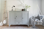 Tall sideboard painted grey and hanging chair in living room