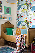 Wooden bed and colourful wallpaper in child's bedroom