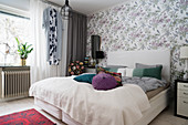 Double bed in bedroom with floral wallpaper