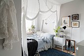 Bed with white curtains and bedside cabinet in cosy bedroom