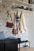 Garderobenhaken und Regale und Sitzwürfel in der Diele mit Tapete