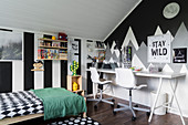 Wide stripes and mountains painted on walls of monochrome child's bedroom