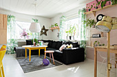 Black sofa in sunny living room with colourful accents