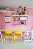 Gelbe Stühle am Schreibtisch vor rosafarbener Wand mit Regalen
