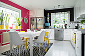 Modern kitchen-dining room with bright pink and yellow accents