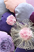 Small round cushions and fabric flowers in various shades of pink and purple