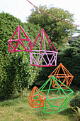 Geometric decorations made from colourful drinking straws in garden