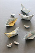 Small paper boats made from folded maps