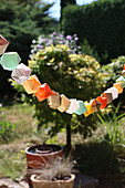 Garland of colourful origami shapes in garden
