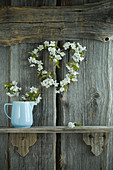 Cherry-blossom heart-shaped wreath on rustic wooden wall and jug of cherry blossoms