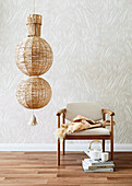 Ceiling lamp made of raffia balls next to an upholstered chair