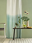 Ombré curtain against pale green wall