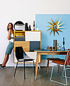 Woman leaning against a chest of drawers in the dining room with retro charm