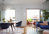 Blue armchairs at dining table and sofa with side tables in open-plan interior