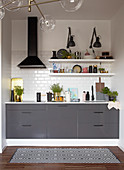 Grey kitchen counter, extractor hood, white wall tiles and shelves