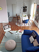 Various chairs, sofa and side table in dining area of open-plan interior