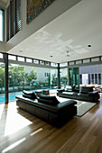 Two sofas facing one another in modern house with glass walls