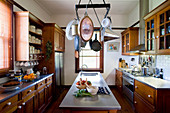 Kitchen utensils on wall-mounted shelving unit in country-house kitchen
