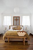 Doppelbett mit Fußbank und symmetrisch angeordneten Nachttischen im Schlafzimmer mit weiß gestrichener Holzverkleidung