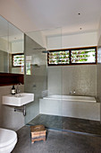 Rainfall shower and bathtub behind glass partition in bathroom with mosaic tiles and ribbon window