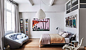 Bedroom with double bed, large-format murals and light gray sofa