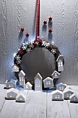Christmas wreath with fairy lights and illuminated paper houses