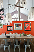 Glasses and candle lanterns on dining table, classic chairs, retro posters on orange partition and pendant lamps
