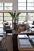 View past books on table to vintage leather sofa with fur blanket and cushions, armchair and houseplant