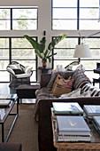 Blick über Tisch mit Büchern auf Vintage Ledersofa mit Felldecke und Kissen, Sessel und Zimmerpflanze