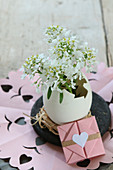 Easter arrangement of duck egg used as vase for small white flowers and origami envelope