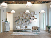 Unusual wall-mounted shelves, rustic wooden ceiling and wooden floor in bright living room
