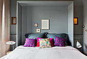 Colourful cushions on grey fold-down bed
