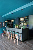 Extravagant, designer, open-plan kitchen in petrol blue and grey